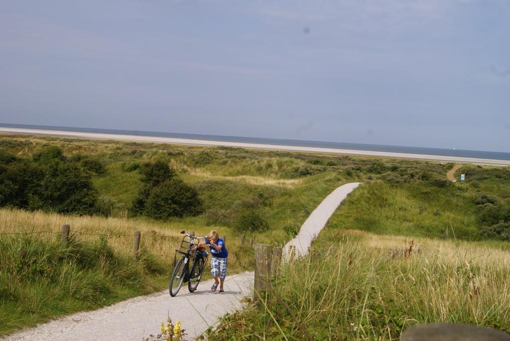 Un niño con la bicicleta en la isla de Schiermonnikoog, Holanda
