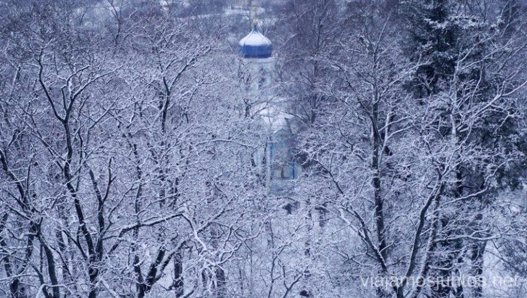 Iglesia entre árboles en Cesis. Viajar a Países Bálticos en invierno.